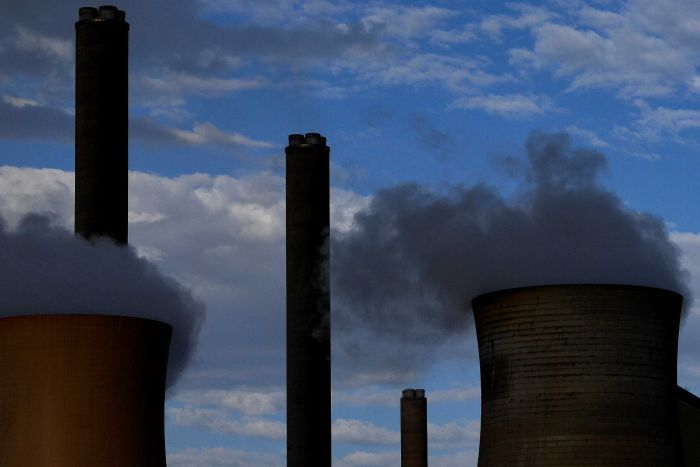 Smoke billows from two towers of a power plant as clouds obscure blue sky in the background.