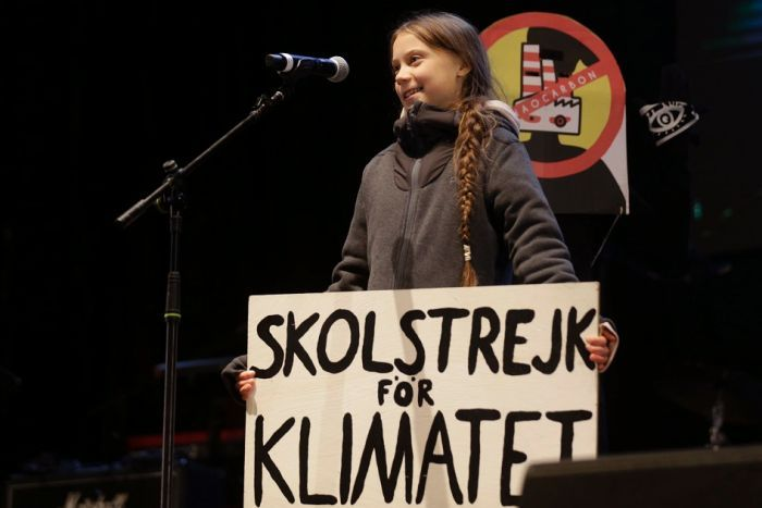 Greta Thunberg wit h a sign speaking in a microphone.