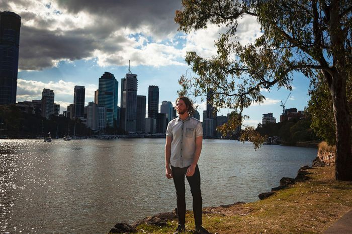 Mark McVeigh stands beside the Brisbane River
