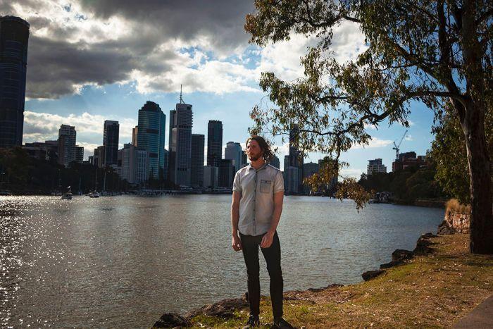 Mark McVeigh stands beside the Brisbane River