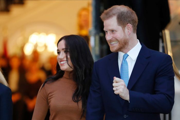 Prince Harry and Meghan, Duchess of Sussex leave a building. Both are smiling excitedly.
