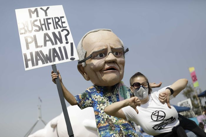 A climate action protester dressed in a Scott Morrison mask and a Hawaiian shirt, holding a placard.