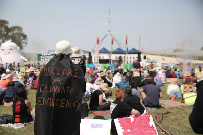 "A campaigner is wearing a black cape with ""declare a climate emergency"" written on it, in front of Parliament House in Canberra."