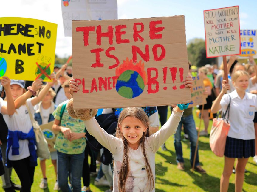 "A girl holds up a sign reading ""there is no planet B"" during a school climate strike in Sydney."