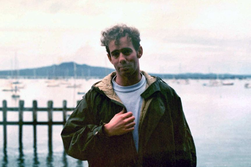 In an old photo Richard Aedy, aged in his 20s, stands in front of a yacht-filled harbour wearing a jacket.