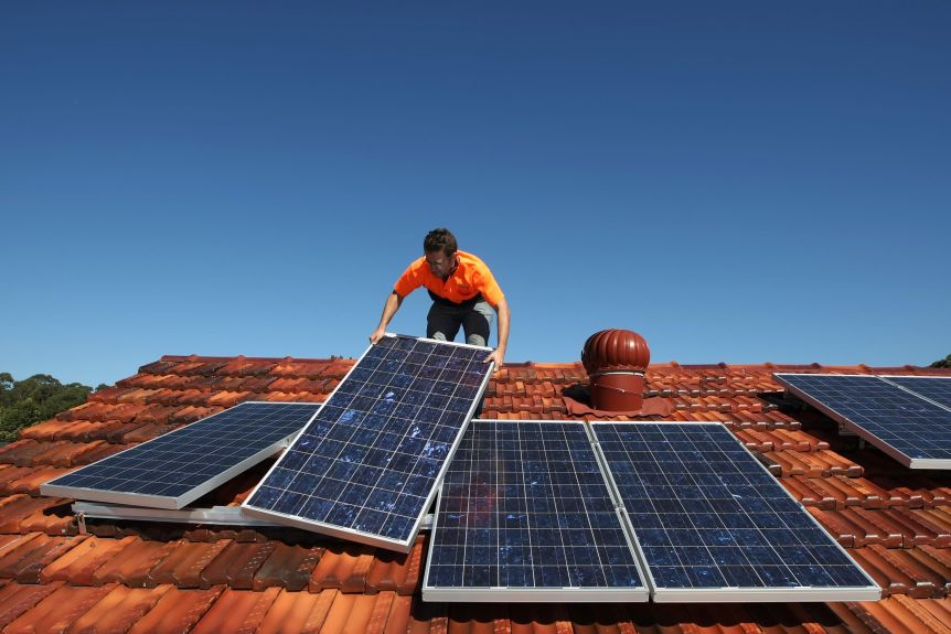 A solar system installer adjusts solar panels on the roof of a house.