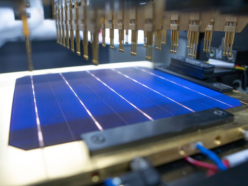 A solar cell being tested with machinery over a blue solar cell.