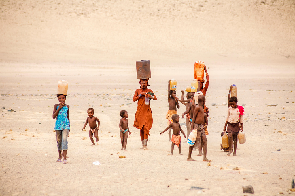 Himba woman and children working carrying water to a village.