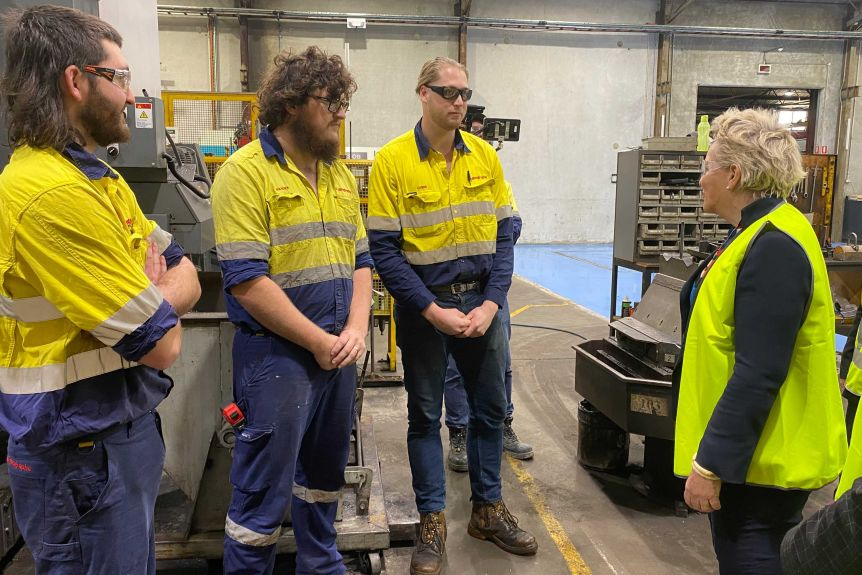 Three young men in high vis work wear talk to a female politician while standing in a workshop.