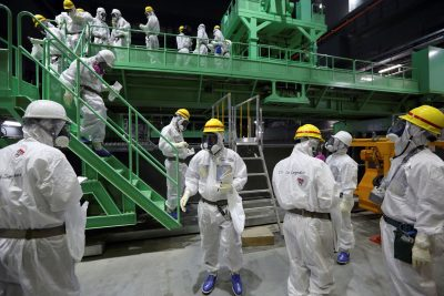 Members of the media and Tokyo Electric Power Co. (TEPCO) employees wearing protective suits and masks walk down the steps of a fuel-handling machine at the spent fuel pool inside the No.4 reactor building at the tsunami-crippled TEPCO's Fukushima Daiichi nuclear power plant in Fukushima prefecture, 7 November, 2013 (Photo: Tomohiro Ohsumi/Pool via Reuters/File Photo).